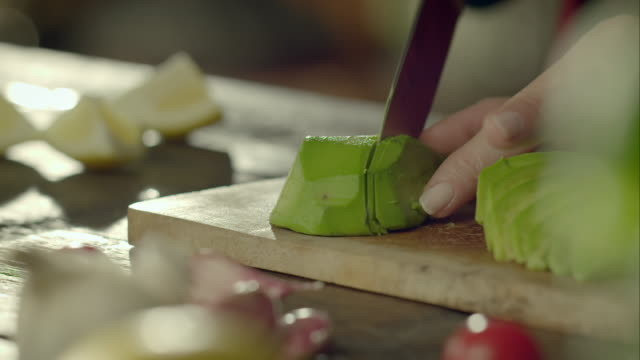Woman cutting avocado into slices video