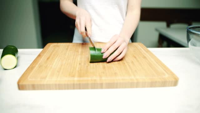 Woman Cutting Zucchini On Wooden Board video