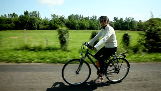 Woman cycling on road in countryside video
