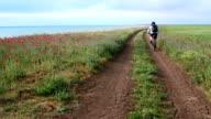 Woman cyclist rides bike along the seashore video