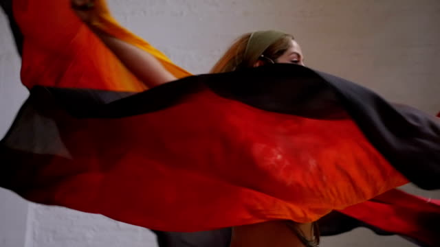 A woman dancer spinning around with flowing fabric in slow motion video
