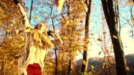 SLO MO Woman dancing under autumn leaves video