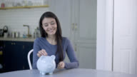 Woman day dreaming and putting coins in piggy bank video
