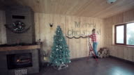 Woman decorating wall for Christmas video