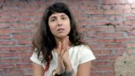Woman depict despair, hopelessness, desolation in camera. Casting. Brick wall video