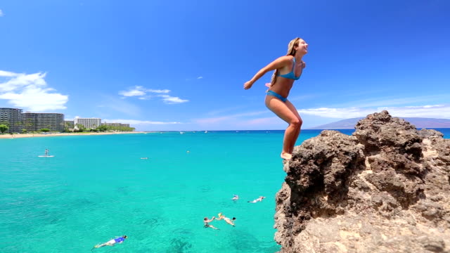 Woman doing a backflip from cliff into the ocean video