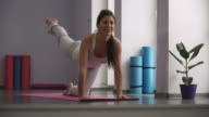 Woman doing exercises for legs on exercise mats video