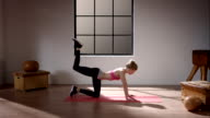 Woman doing her workout in gym (quadruped position leg extension) video