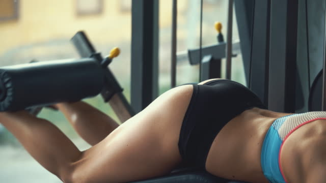 Woman doing leg curls at gym. video