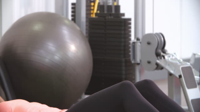 Woman doing medicine ball sit-ups with a trainer in a gym video