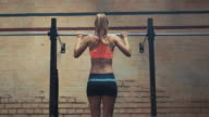 Woman doing pull-ups in gym video