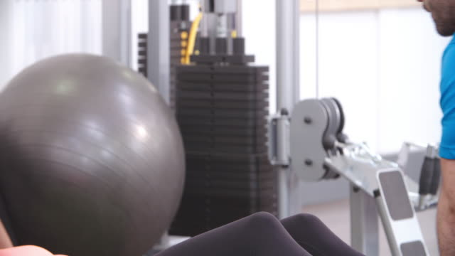 Woman doing sit-ups with a medicine ball in a gym, close up video