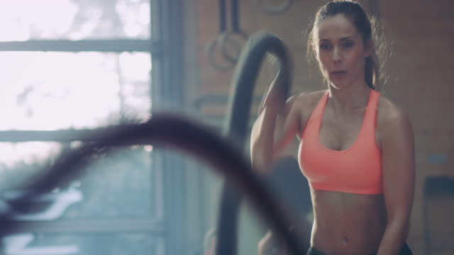 Woman doing tough workout with ropes video