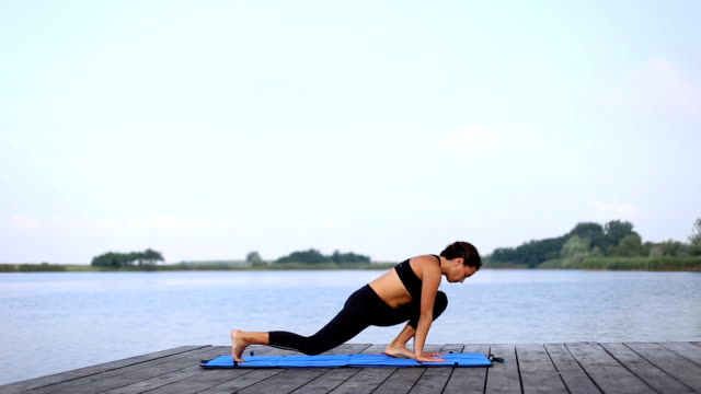 A woman doing yoga by the lake video