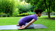Woman doing yoga in the garden - streching video