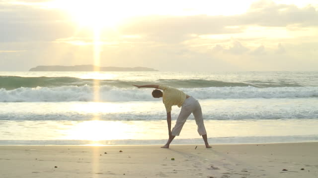 HD: Woman doing yoga on the beach at sunrise video