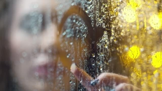 Woman Drawing Heart on Window Pane video