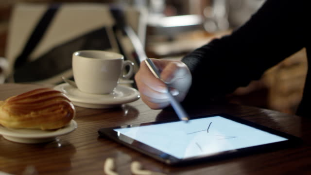 Woman Drawing on Tablet PC in Coffee Shop video