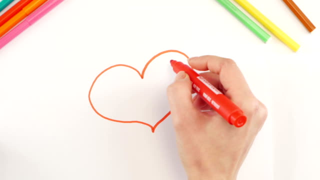 Woman drawing the heart using red felt-tip pen on white paper, time lapse video