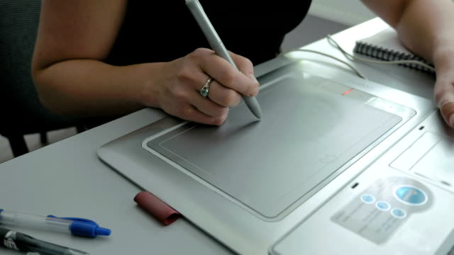 A woman draws with pen tablet digitizer and stylus video