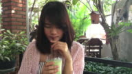 Woman drink green tea frappe with tube in glass cup. video