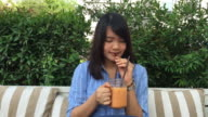 Woman drink tea frappe with tube in glass cup. video