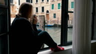 Woman drinking coffee and looking at Venice view video