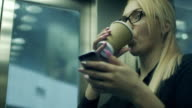Woman Drinking Coffee and Using Mobile Phone in Cafe video