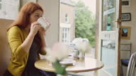 Woman Drinking Coffee in Sunlit Cafe video