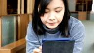 Woman drinking coffee / tea and using tablet in a coffee shop video