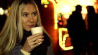 Woman drinking hot drink on the Christmas Fair video