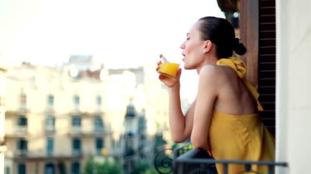 Woman drinking orange juice on the balcony video
