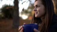 Woman drinking tea in the park in autumn. video