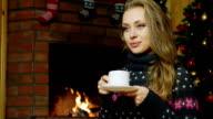 Woman drinking tea near the fireplace video