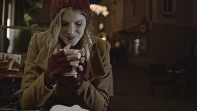 Woman drinking tea outside of a cafe video