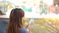 Woman drinking water after excercise in park video
