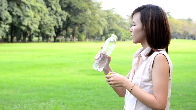Woman Drinking Water In The Park video