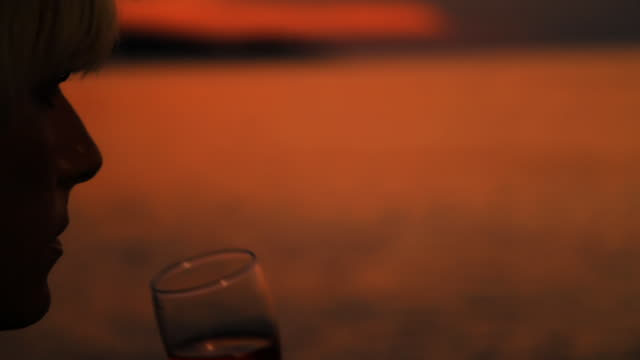 HD DOLLY: Woman Drinking Wine On The Beach At Dusk video
