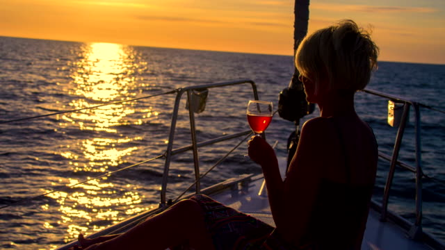 MS Woman Drinking Wine While Sailing At Sunset video
