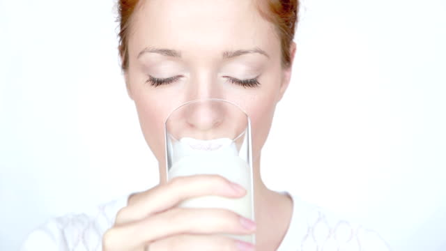 Woman drinks milk and lick off white mustache video