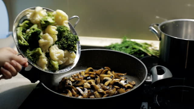 Woman drops colorful broccoli, pea, cauliflower to the pan with button mushrooms. Slow motion video