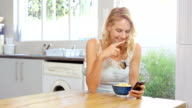 Woman eating cereal while looking at smartphone video