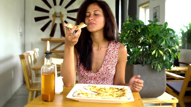 Woman eating cheese pizza slice video