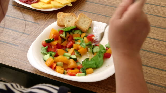 Woman eating summer vegetable salad outdoors video