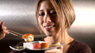 Woman eating sushi - stainless steel background. video