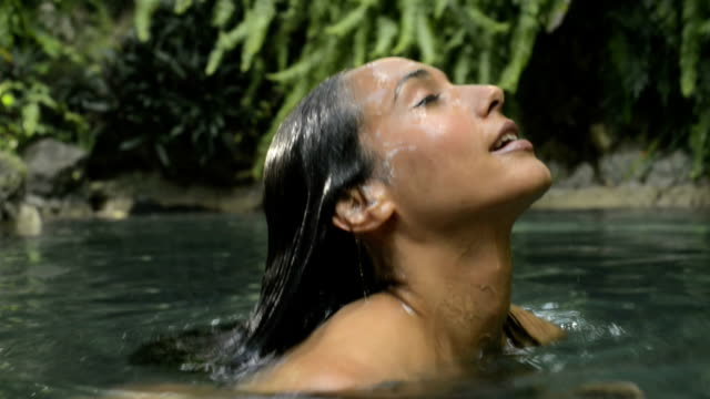 Woman emerging from the water in a natural pool video