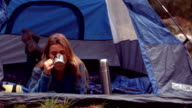 Woman enjoying hot drink in her tent video