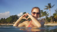 Woman enjoying in the sea forming a heart with hands video