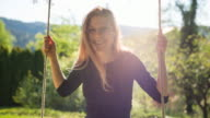 Woman enjoying nature, swinging on a rope swing with greenery in background video