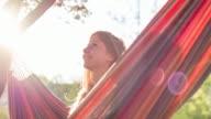 Woman enjoying summer in nature, sitting in a hammock video